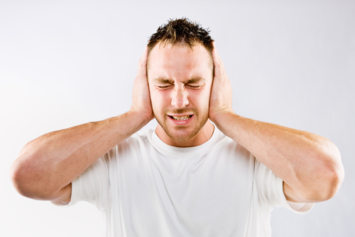 Man blocking out loud noise from ears.