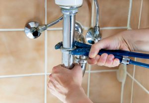 Hands of a plumber with a sink and a wrench.